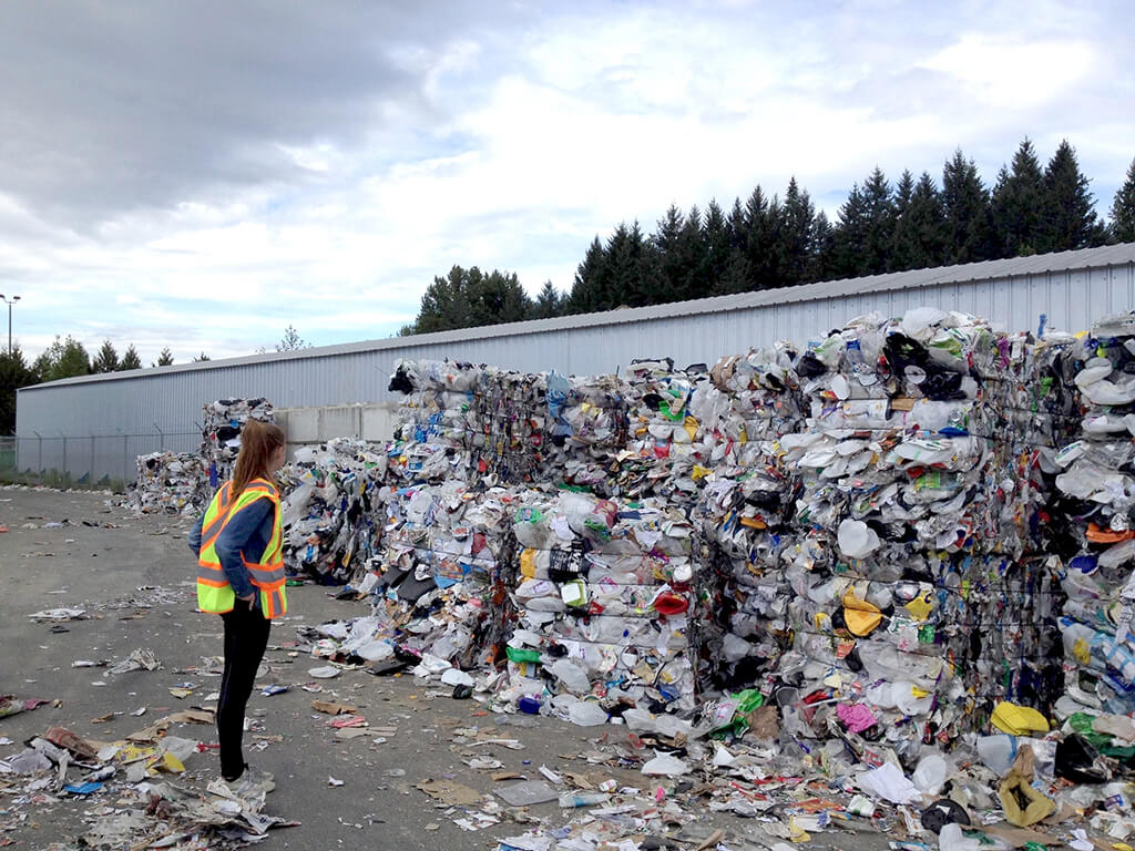 An employee of a recycling center stares at towering piles of compacted recycling.