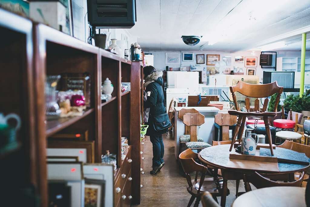 Woman browsing a second-hand shop, between cabinets and tables.