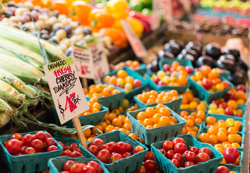 A display of organic cherry tomatoes advertises $4.00/box.