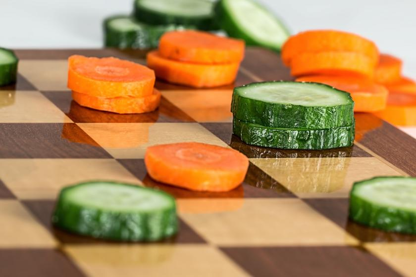 Cucumbers and carrots have replaced the pieces on a chess board.