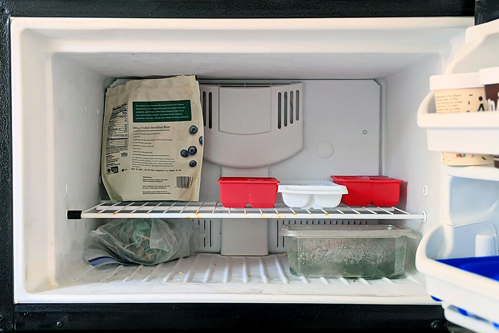 An open freezer that stores ice, frozen berries, and ice cream