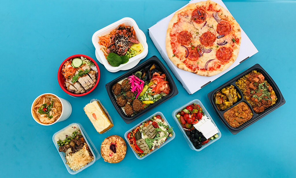 A spread of prepared food, including pizza, falafel, Indian food, salad, and desserts