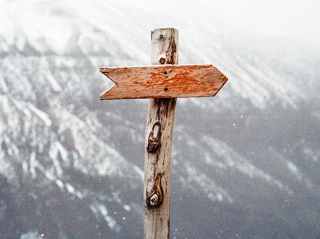 A wooden arrow pointing to the right, backed by snowy mountains